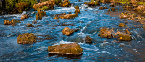 small mountime river.A pair of river rocks with a small waterfall