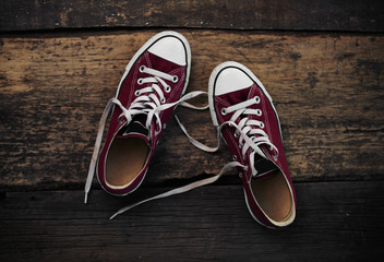 Red footwear of teenage girl on wooden floor. Concept of youth, lifestyle and travel.
