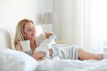 Fototapete - happy woman with coffee and cat in bed at home