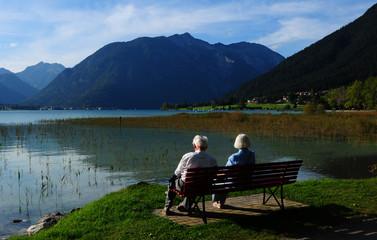 Ein älteres Paar sitz auf einer Bank am Ufer des Achensee's im Tirol.