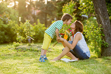 Young beautiful mother, sitting in a garden, little boy, her son