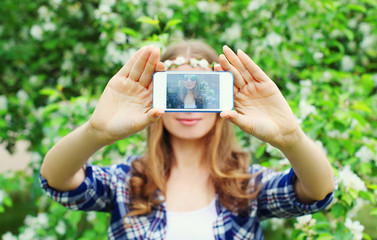 Woman makes self portrait on smartphone view of screen in spring