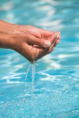 mains prenant de l'eau dans une pisicne