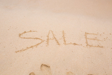 Summer sale handwritten in sand on a beach
