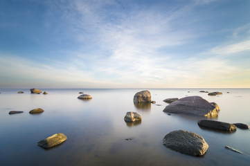 sea landscape, boulders in the water,sunset and colorful sky, slow shutter speed