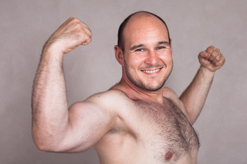 Closeup of happy naked man showing his strong arms