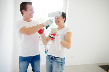 Young man and woman have fun during repair in the house.