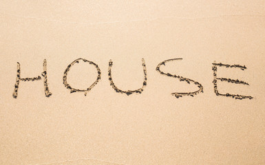 word house written in sand on beach