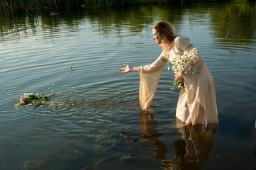 Pretty young woman in traditional dress puts wreath in water of lake. Russian traditional Ivan Kupala holiday celebration