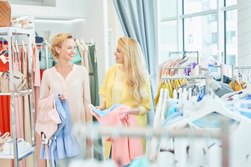 Portrait of two girls with the clothes in hand in a clothing store