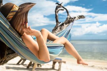 Frau im Urlaub am Strand entspannt in Hängematte am Meer