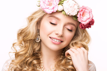 Close-up portrait beautiful girl with wreath of flowers. Touching hair, eyes closed