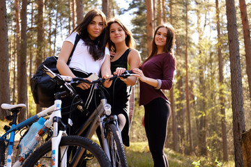 Thre sporty females posing with bicycles in a forest.
