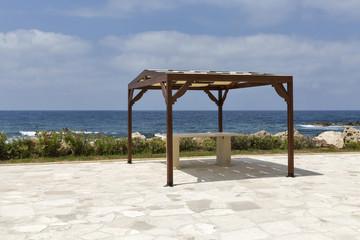Empty pavilion on rocky sea beach Wall mural
