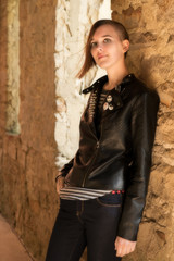Teenaged girl with short hair and a leather jacket leaning against a stone wall.