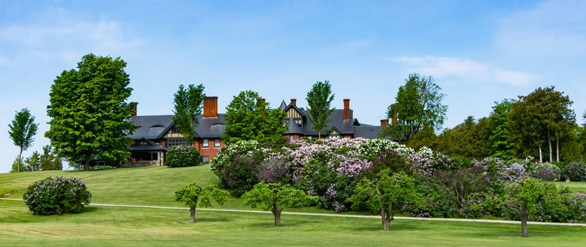 spring lilacs in full bloom in front of historic Inn at Shelburne Farms, Vermont