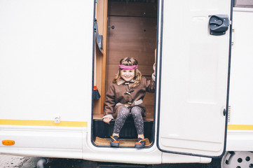Blonde girl sitting in a caravan