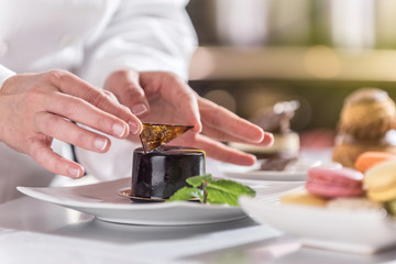 closeup on hands of a pastry chef depositing a chocolate leaf