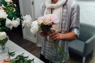Male florist preparing bouquet of peones