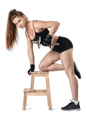 Cutout portrait of muscular young woman lifting a dumbbell for training her back muscles leaning on the chair
