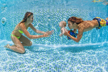 Child swimming lesson - baby with mother, father learn to swim, dive underwater in swimming pool. Healthy active family lifestyle, physical exercise, water sport activity with parent on summer holiday