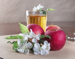 red apples and glass of cider on the wooden table with white flo