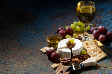 Camembert cheese, snacks and a glass of white wine