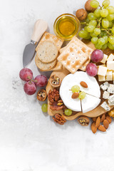 camembert, grapes and snacks on a white background, vertical