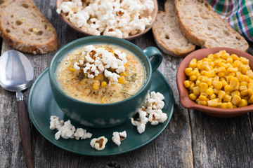 corn soup with popcorn in cup on wooden table
