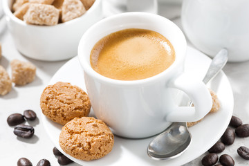 cup of espresso and cookies on a white table, closeup