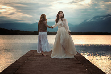 Beautiful women walking on lake pier