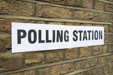 British election polling station sign hanging on classic yellow brick wall in London, UK