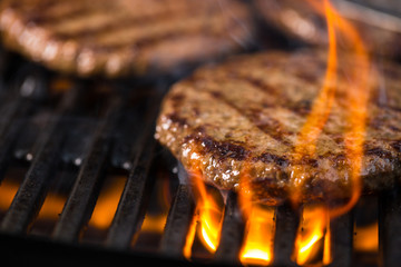 Verschillende hamburgers op het grillrek met vlammen op de voorgrond