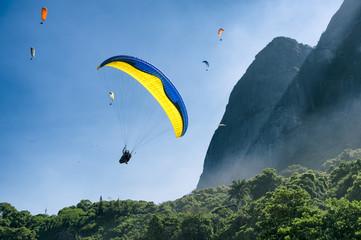 Paraglider passes along the misty greenery of Pedra da Gavea Mountain on its way to land at São Conrado Beach in Rio de Janeiro, Brazil