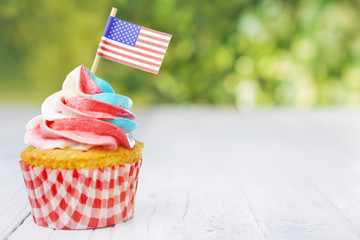 Cupcake with red-white-and-blue frosting and an American flag