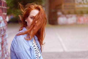 frau mit verwehten roten haaren