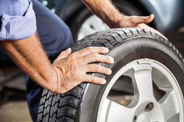 Mechanic Holding Car Tire At Garage
