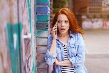 frau telefoniert und schaut überrascht