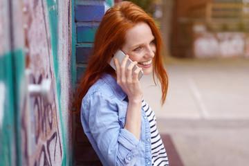 frau steht draußen an einer backsteinwand und telefoniert mit ihrem handy