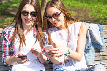 Teen girls using their phones. Young happy teenagers having fun in summer park.
