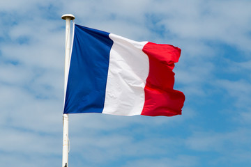 France flag on mast and against blue sky