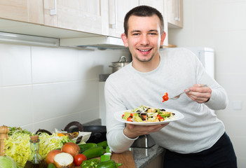 Man eating vegetable salad in kitchen.