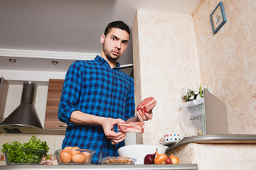 young man preparing meat in her kitchen , looking into the card , the meat in his hand