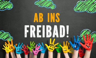 """angemalte Kinderhände vor Kreide-Wolkenhintergrund mit Spruch """"Ab ins Freibad!"""""""
