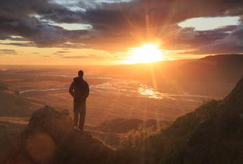 Printed roller blinds Deep brown Man standing on a ledge of a mountain, enjoying the beautiful sunset over a wide river valley in Thorsmork, Iceland.