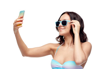 woman in swimsuit taking selfie with smatphone