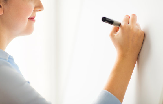 close up of woman writing something on white board