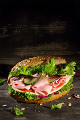 Sandwich with vegetables, ham and cheese on dark wood background, upright