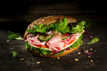 Sandwich with vegetables, ham and cheese on dark wood background