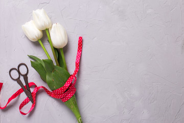 Bunch of white tulips flowers with red ribbon and scissors on gr